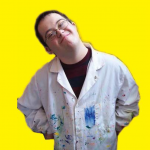 Smiling artist in paint covered smock